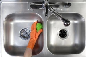 Kitchen sink being cleaned with rubber gloves
