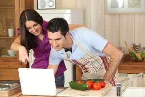 Couple Cooking While On The Computer