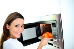 Woman Putting Plate Into Microwave